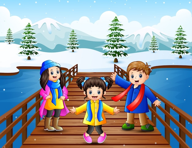 雪の丘の橋の上で幸せな子供