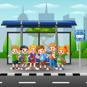 幸せな子供たちのバス停でのイラスト