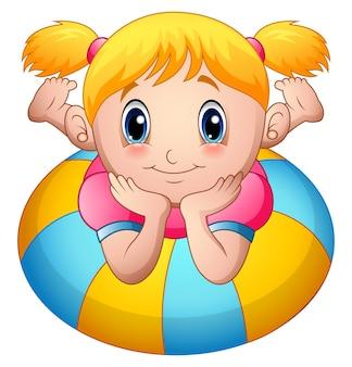 小さな女の子の漫画は、インフレータブルリングの上に横たわる