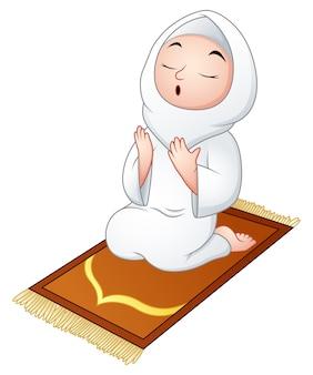 祈りながら祈りの敷物に座っているイスラム教徒の女の子