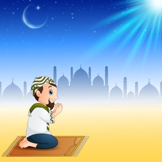 祈りながら祈りの敷物に座っているイスラム教徒の男性