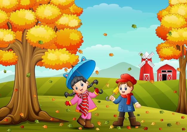 秋の農場風景で遊んでいる子供たち
