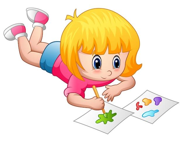 紙の上に横たわって絵を描く小さな女の子