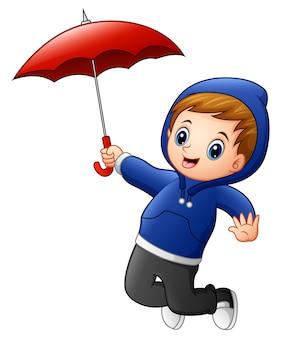 Маленький мальчик с прыжком в красный зонтик