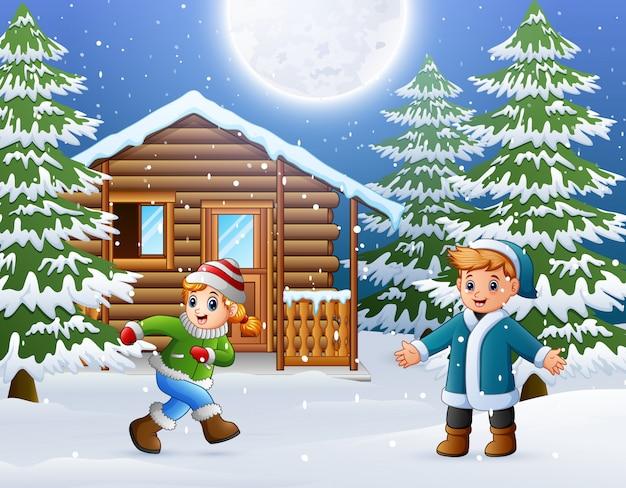 幸せな子供たちが雪の木製家の前で遊ぶ