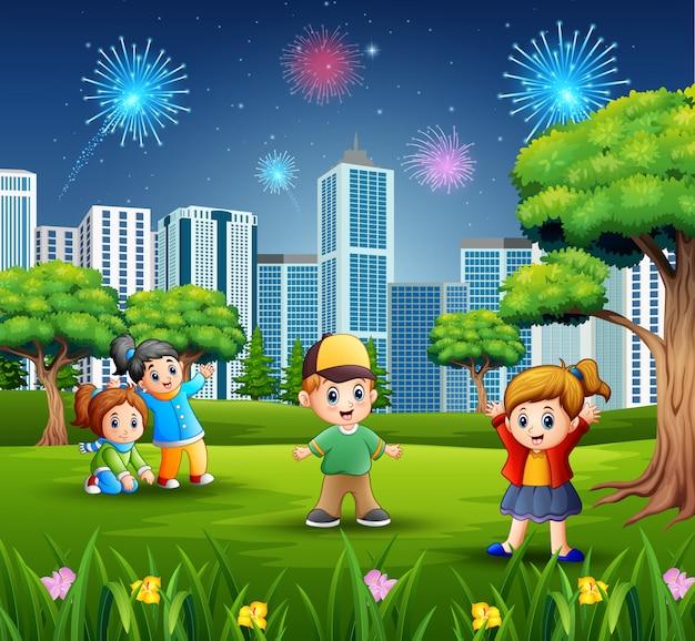 都市の景観と花火で野外で遊ぶ子供たち