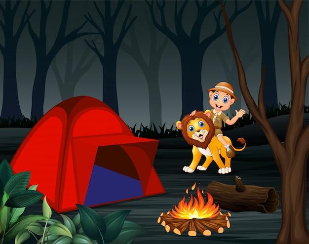 飼育係の少年と夜のキャンプ場でライオン
