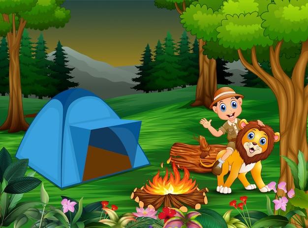 飼育係の少年とテントとたき火の横にあるライオン