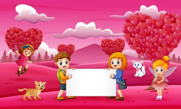 女の子と男の子のピンクの庭でホワイトボードを保持