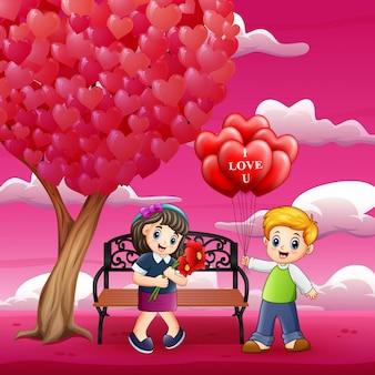 女の子に赤いハート型の気球と花を与える男の子