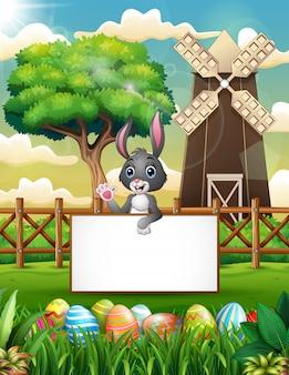 Мультфильм кролик, махнув рукой с пустым знаком в ферме