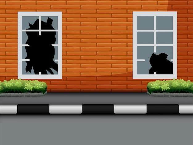 Окно с битым стеклом на красной кирпичной стене