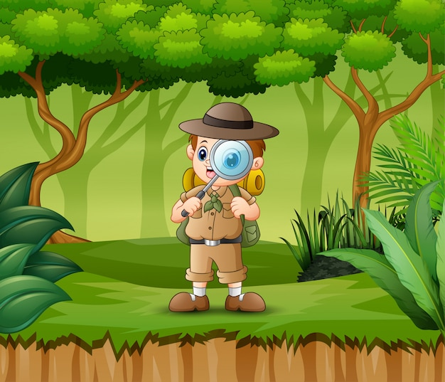 Мальчик исследователь с увеличительным стеклом в лесу