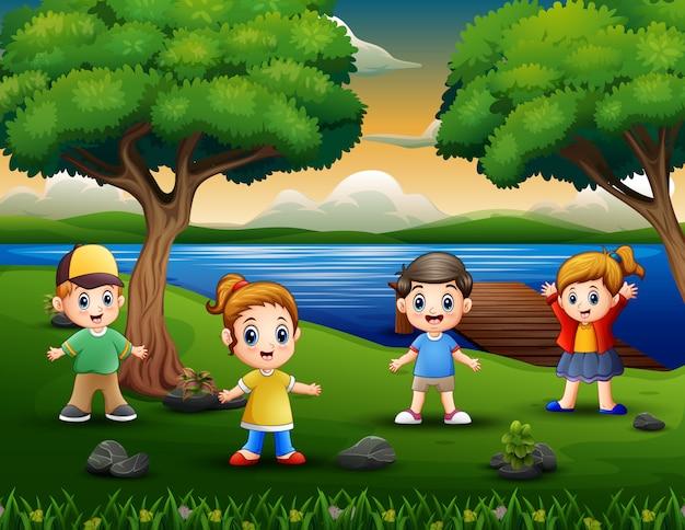 Счастливые дети играют на берегу реки