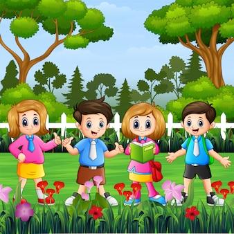 幸せな学校の子供たちが公園に立っています。