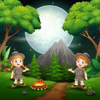幸せなスカウトの男の子と女の子、夜にキャンプファイヤーを