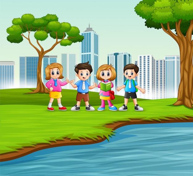 都市公園で遊んでいる幸せな学校の子供たち