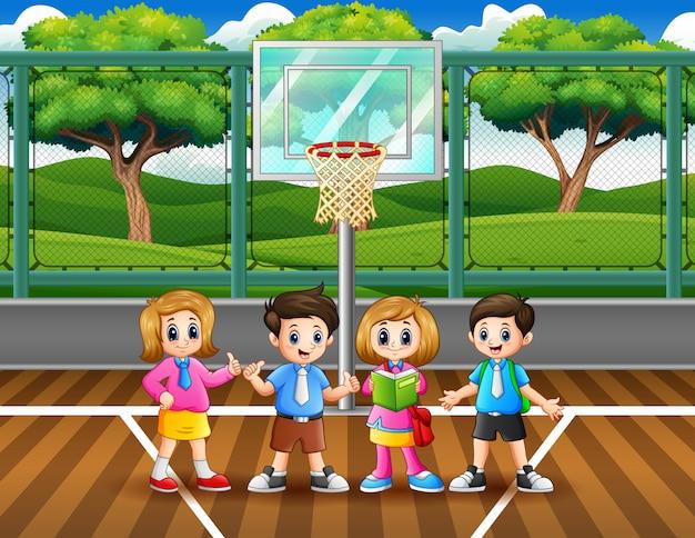 バスケットボールコートで幸せな学校の子供たち
