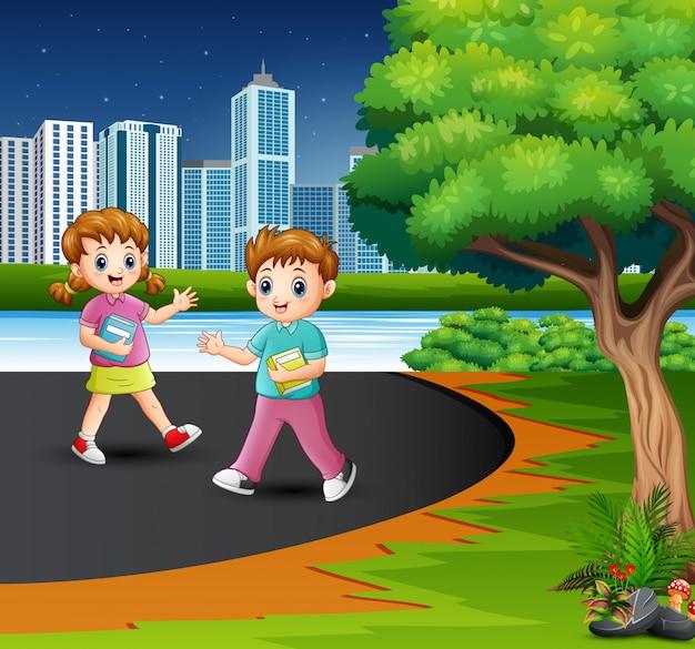 幸せな学校の子供たちが道を歩いています。