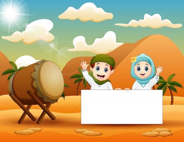 砂漠で空白記号を保持しているかわいいイスラム教徒の子供