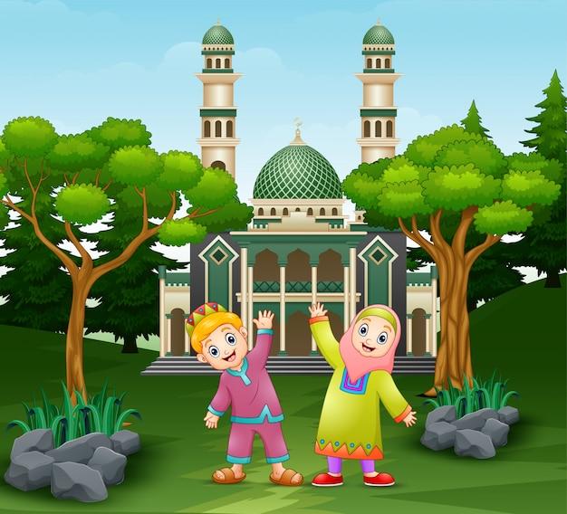幸せな子供たちはモスクの前でポーズをとっています。