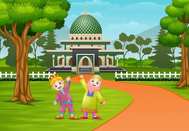 モスクの前でポーズをとって幸せなイスラム教徒の子供