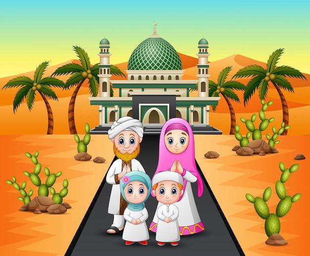 砂漠のモスクの前にイスラム教徒の家族