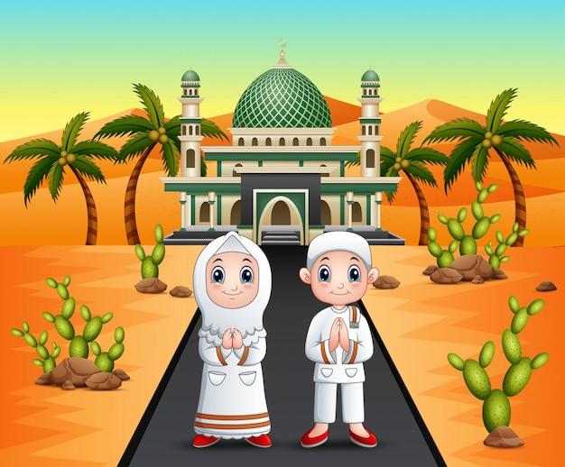 砂漠のモスクの前にイスラム教徒のカップル