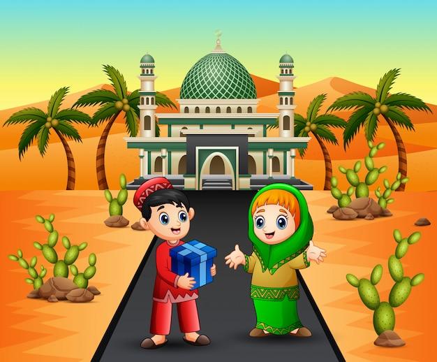モスクの前の女の子にプレゼントを与えるかわいいイスラムの男の子