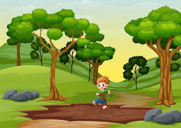 泥の水たまりで遊ぶ少年