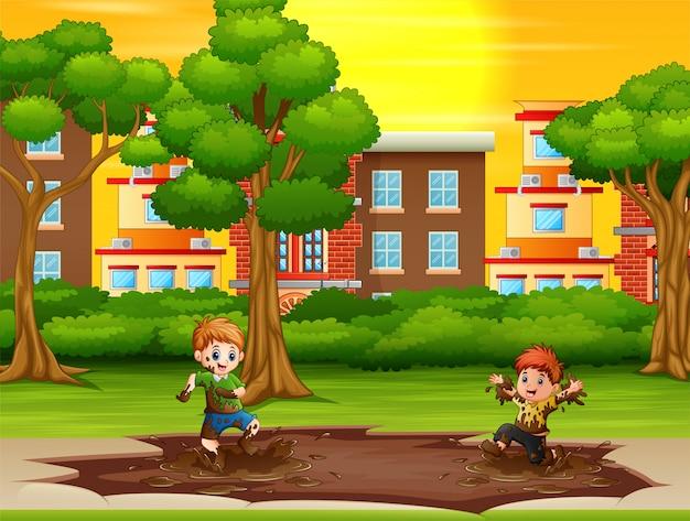 都市公園における泥の水たまりを遊んでいる子供たち