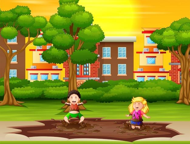 Дети играют в грязную лужу в городском парке
