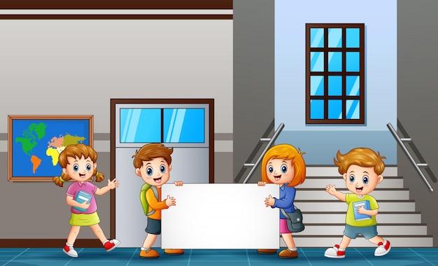 学校の子供たちが教室の前に空白の看板を持っています。
