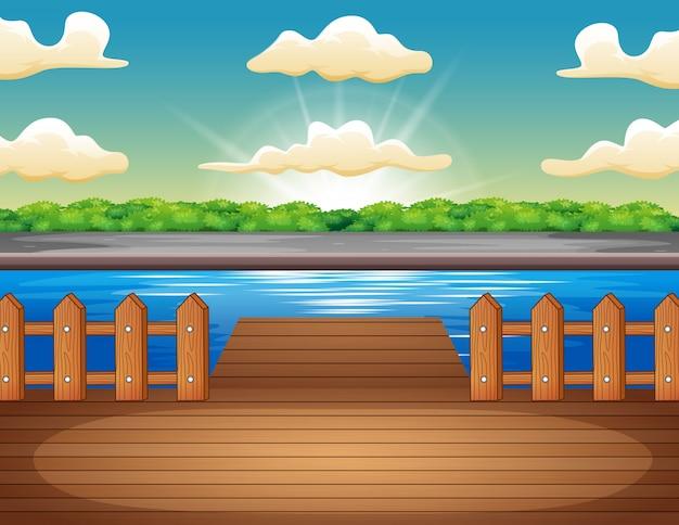 日の出で湖を見下ろす木製の桟橋