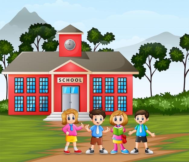 学校の建物の背景に幸せな小さな子供