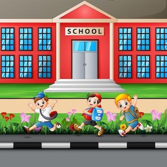Счастливые мальчики с рюкзаком идут в школу