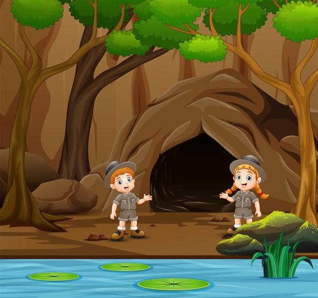 スカウトの男の子と女の子が洞窟の近くで話しています。