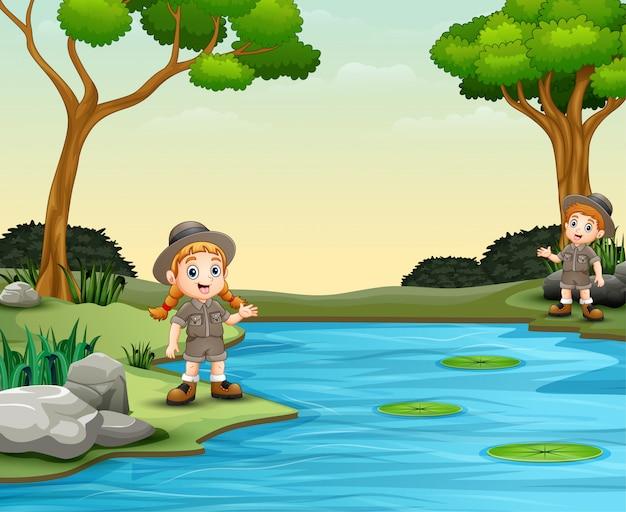 スカウトの男の子と女の子が川で話しています。