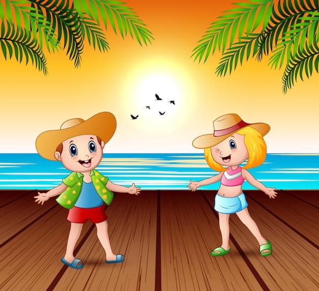 Счастливые дети на пристани и глядя на закат пейзаж