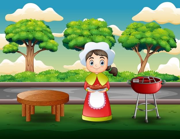 屋外バーベキューグリルでステーキを保持している若い女性