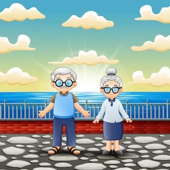 Счастливая старая пара стоит возле моря