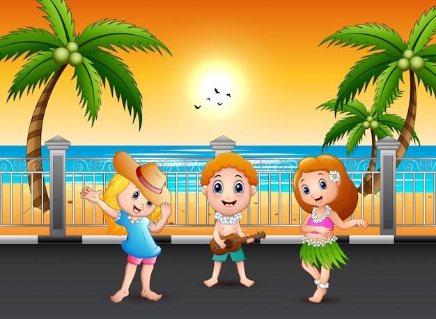 ギターを弾く少年とハワイアン女の子フラ海辺で踊る
