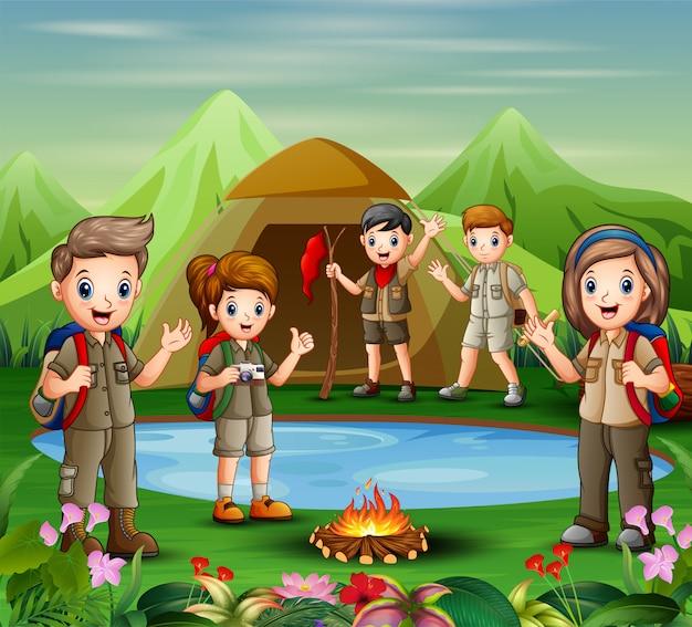 若いスカウトの女の子と男の子のグループは、自然の中で探索しています