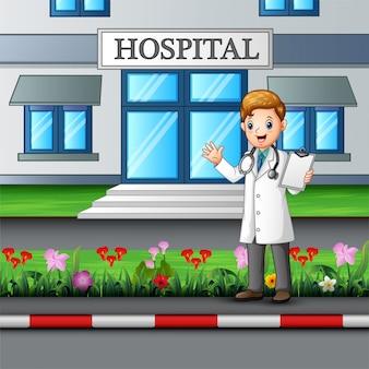 病院の建物の前に立っている若い医者