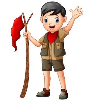 赤い旗を保持しているスカウト少年を漫画します。