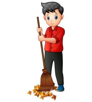 ほうきを持つ男は落ち葉を掃除します