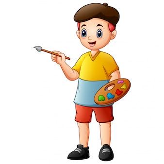 絵筆と水彩絵の具を保持している創造的な少年