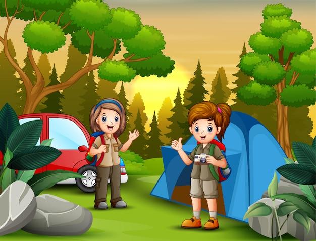 キャンプ場で探検家の女の子と夕日の風景