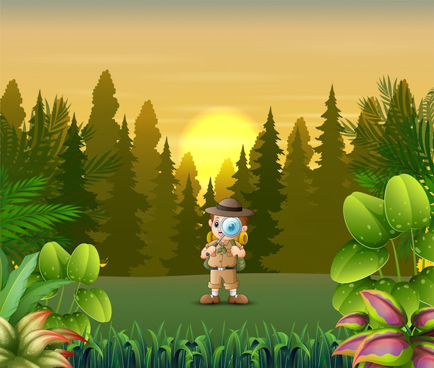 Исследователь мальчик с увеличительным стеклом в лесу