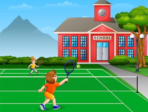 Показывая мальчика и девочку, играющих в теннис на школьном корте